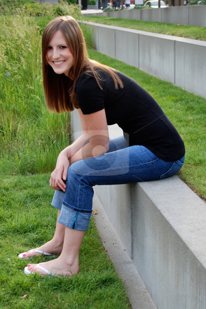 Teen Sitting on Wall - Vertical, Smiling stock photo, Vertically framed outdoor side-shot of a smiling teenage girl sitting on wall in field with green grass. by Orange Line Media