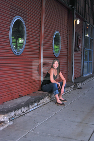 Teen Sitting on Curb next to Bulding stock photo, Outdoor shot of a smiling teenage girl sitting on a curb next to red building with round windows. by Orange Line Media