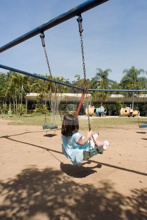 Little Girl Swinging stock photo, Cute little girl playing on a swing on a sunny day. Vertically framed shot taken from behind the little girl. by Orange Line Media