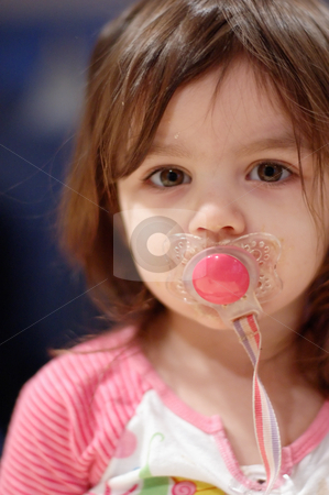 Cute Young Girl with Pacifier stock photo, Cute young girl with a pacifier in her mouth. Vertically framed close-cropped shot. by Orange Line Media