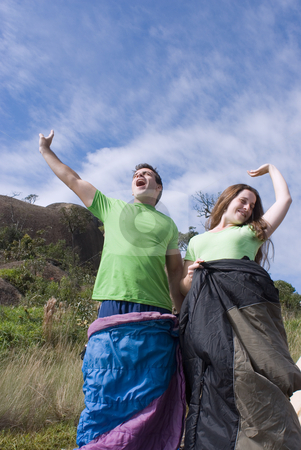Waking Up Outdoors - Vertical stock photo, Vertically framed outdoor shot, looking up towards the sky, of a young attractive couple standing in their sleeping bags yawning as they awake from their slumber. by Orange Line Media