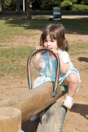 Cute Little Girl stock photo, Adorable little girl playing on a see-saw. Vertically framed shot. by Orange Line Media