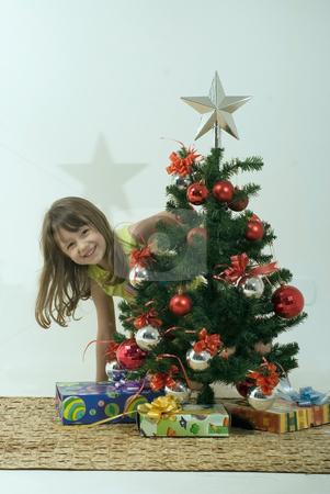 Smiling Girl and Christmas Tree stock photo, Smiling girl peeking out behind a christmas tree. by Orange Line Media