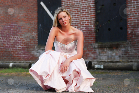 Bridesmaid Crouched in Front of Brick Wall - Horizontal stock photo, Horizontally framed outdoor shot of an attractive bridesmaid crouching down in front of red brick wall. by Orange Line Media