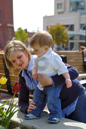 Flowers, Mother, Son - II stock photo, Mother and baby son, standing with her support, looking at tulip flowers. by Orange Line Media