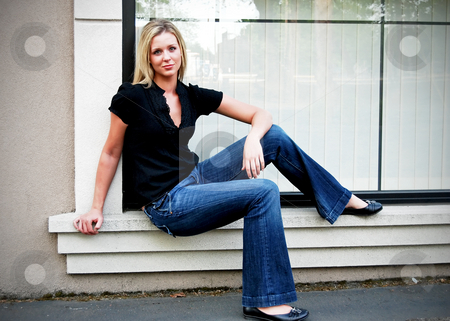 Cute Blond stock photo, Attractive blond woman sitting on a window ledge dressed casually in a black top and blue jeans. Horizontally framed shot. by Orange Line Media