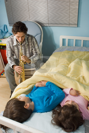 A Father Playing a Clarinet/Oboe for Children during Bedtime stock photo, A father playing a clarinet/oboe for children in bed. by Orange Line Media
