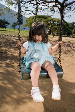 Little Girl Swinging stock photo, Cute little girl playing on a park swing on a sunny day. Vertically framed, wide angle shot. by Orange Line Media
