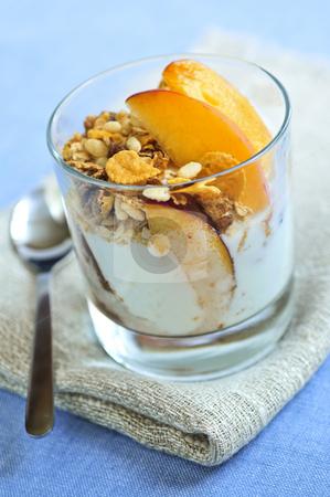 Serving of yogurt and granola stock photo, Serving of yogurt with fresh peaches and granola by Elena Elisseeva