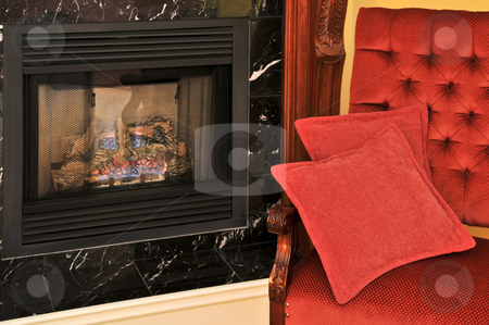 Fireplace and red chair stock photo, Fireplace and red chair in living room by Elena Elisseeva