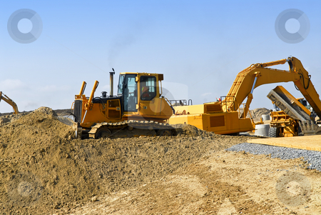 Construction site machines stock photo, Yellow bulldozer machines digging and moving earth at construction site by Elena Elisseeva