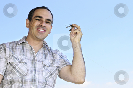 Man holding keys stock photo, Smiling man holding house keys on blue sky background by Elena Elisseeva
