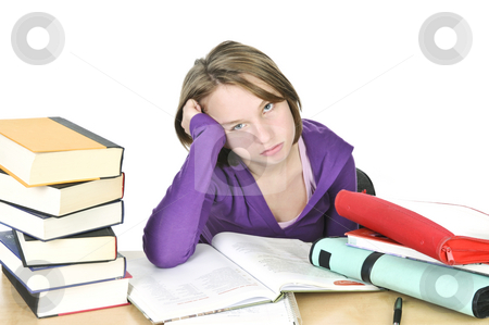 Teenage girl studying stock photo, Unhappy teenage girl studying at the desk by Elena Elisseeva