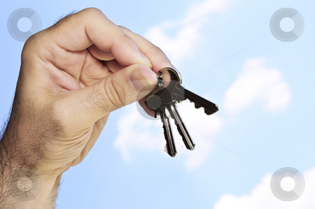 Hand holding keys stock photo, Man's hand holding house keys on blue sky background by Elena Elisseeva