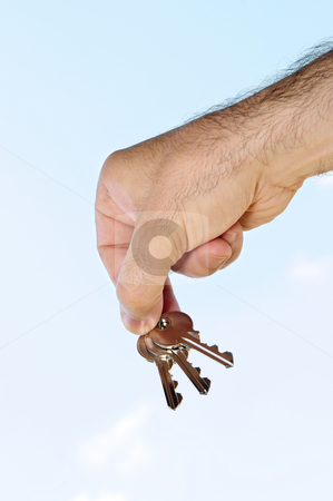Hand holding keys stock photo, Man's hand holding house keys on blue sky background by Elena Elisseeva