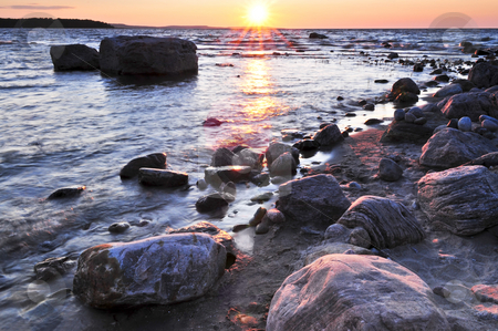 Sunset over water stock photo, Sunset at the rocky shore of Georgian Bay, Canada. Awenda provincial park. by Elena Elisseeva