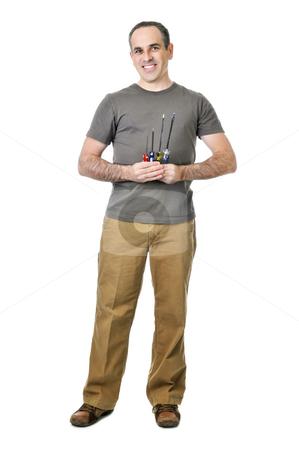 Handyman with screwdrivers stock photo, Smiling handyman holding a bunch of screwdrivers by Elena Elisseeva