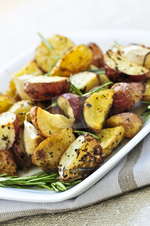 Roasted potatoes stock photo, Herb roasted potatoes served on a plate by Elena Elisseeva