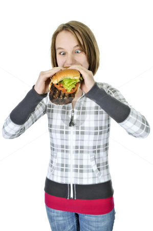 Teenage girl eating big hamburger stock photo, Teenage girl eating a big hamburger isolated on white background by Elena Elisseeva