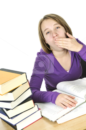 Teenage girl studying stock photo, Yawning teenage girl studying at the desk by Elena Elisseeva