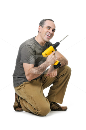 Handyman with a drill stock photo, Kneeling happy handyman with his cordless drill by Elena Elisseeva