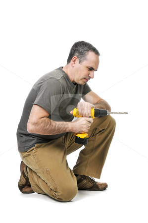 Handyman with a drill stock photo, Kneeling handyman pushing on his cordless drill by Elena Elisseeva