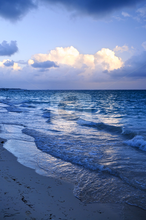 Ocean waves on beach at dusk stock photo, Ocean waves on beach at dusk with sunlit clouds by Elena Elisseeva