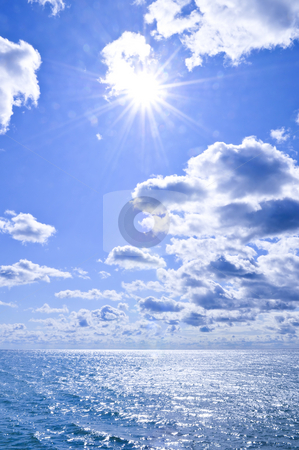 Blue water and sunny sky background stock photo, Blue ocean water and sunny sky background by Elena Elisseeva