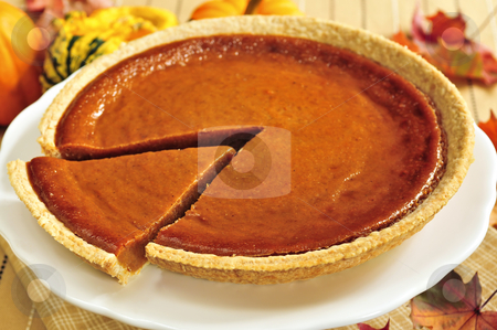 Pumpkin pie stock photo, Whole pumpkin pie with a slice cut out by Elena Elisseeva