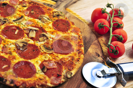 Pepperoni pizza stock photo, Freshly baked pepperoni pizza on wooden board by Elena Elisseeva
