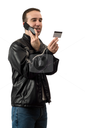 Telephone Banking stock photo, A young man doing some telephone banking and giving the bank his debit card number, isolated against a white background by Richard Nelson