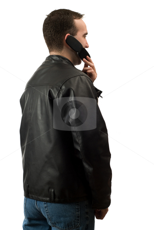 Casual Man On Cellphone stock photo, A young man wearing a leather jacket is facing away from the camera and talking on his cellphone, isolated against a white background by Richard Nelson