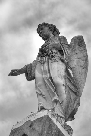 Cemetery Angel stock photo, A statue of a mourning angel under moody skies atop a tomb in New Orleans. by A Cotton Photo