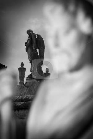 Selective Focus Grave Statues stock photo, Black and White selective focus image of an angel adorning an above ground tomb with the statue of a man in the foreground. by A Cotton Photo