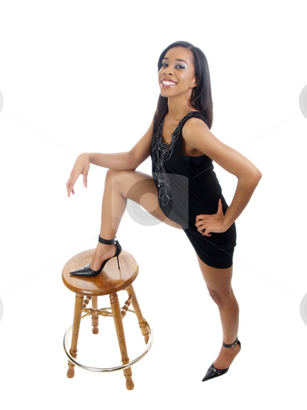 Young black woman with foot on top of stool stock photo, Young black woman in dress in bold stance leg on stool by Jeff Cleveland