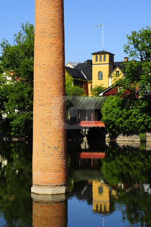 Town by the water stock photo, Old city of Norrkoping with chimney in the water by Magnus Johansson