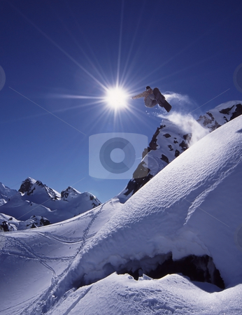 Freeride snowboard stock photo, Snowboarder jumps high in dramatic mountain scene with white snow and clear blue sky. by Magnus Johansson