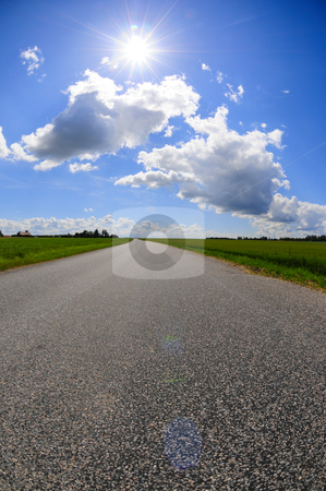 Sky road stock photo, Beautiful sunlight above countryside road by Magnus Johansson