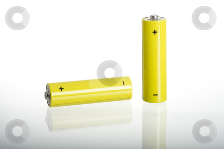 Batteries stock photo, Two yellow batteries, isolated on white, reflection on glass by mdphot