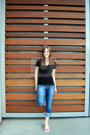 Teen Leaning Against Teak Paneling - Vertical, Smiling stock photo, Vertically framed outdoor shot of a smiling teenage girl leaning against a Teak paneled wall. by Orange Line Media