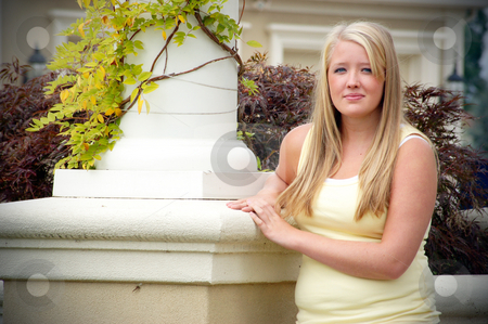Teen Standing next to Pillar stock photo, Outdoor shot of a smiling teenage girl, with blond hair and blue eyes, standing next to a white pillar coved in vines wearing a yellow tank-top. by Orange Line Media
