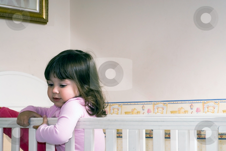 Young Girl stock photo, Adorable young girl climbing around the guardrail of a bedroom crib by Orange Line Media