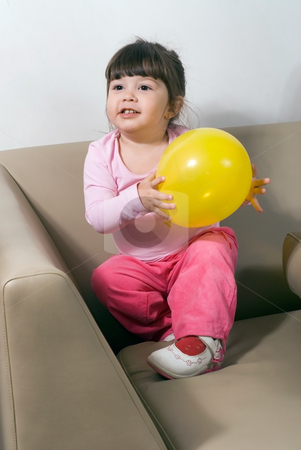 Girl with Yellow Balloon stock photo, Cute young girl playing with a bright yellow balloon on a couch in her living room by Orange Line Media