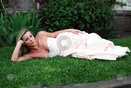 Cute Blond Woman - Horizontal stock photo, Attractive blond woman in a bridesmaid's dress lying on a lush green lawn propping her head up on her hand. Horizontally framed shot. by Orange Line Media