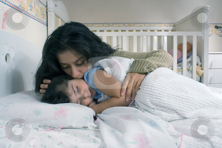 Mother and Daughter stock photo, Mother saying goodnight and tucking her daughter into bed by Orange Line Media