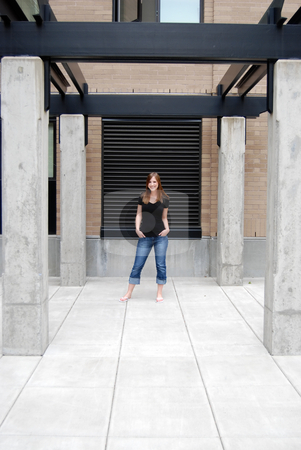 Smiling Teen in Courtyard - Vertical stock photo, Vertically framed outdoor shot of a smiling teenage girl standing in courtyard. by Orange Line Media