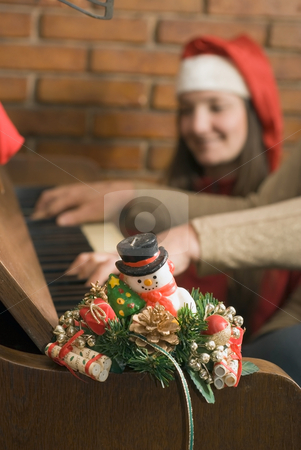 A Christmas candle and Piano stock photo, A Christmas candle sitting on a piano, two people sitting behind. by Orange Line Media