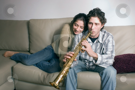 Couple in the Living Room stock photo, Cute young couple in their living room sharing a tender moment. She is hugging him while he is playing a soprano saxophone by Orange Line Media