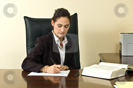 Female Executive stock photo, Businesswoman wearing a blazer sitting at her desk in her office and writing on her notepad. Horizontally framed shot. by Orange Line Media