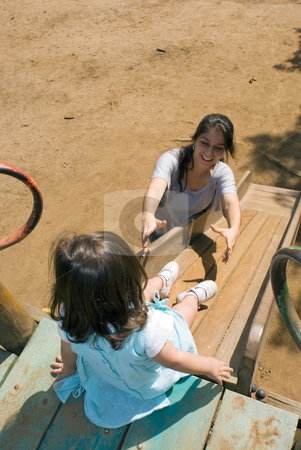 Mother Helping Her Daughter Down a Slide stock photo, Horizontally framed outdoor shot of a smiling mother, with her arms outstretched, coaxing her young daugther down a slide. by Orange Line Media